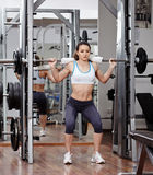 Athletic woman doing squats at the gym Royalty Free Stock Images