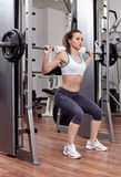 Athletic woman doing squats at the gym Stock Images