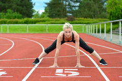 Athletic woman doing straddle stretches on track Royalty Free Stock Photography
