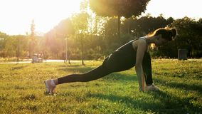 Athletic woman doing stretching exercises in the park at sunset. Fitness, aerobic training, healthy and sporty lifestyle stock video