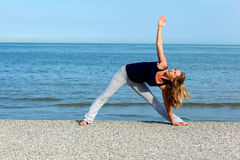 Athletic woman doing yoga exercises at the seaside Stock Photo