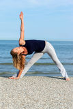 Athletic woman doing yoga training on the beach Royalty Free Stock Images
