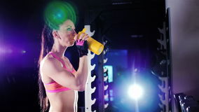 Athletic woman drinking a protein shake in a shaker in the gym. In the rays of spotlights. stock video footage