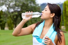 Athletic woman drinking water Stock Images