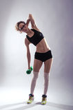 Athletic woman with dumbbell in hand makes the slopes. Sport you Royalty Free Stock Photography