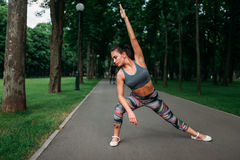 Athletic woman exercises, fitness training in park Royalty Free Stock Photos