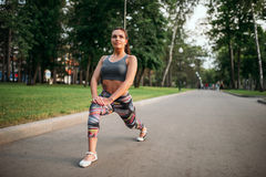 Athletic woman exercises, fitness training in park Stock Photography