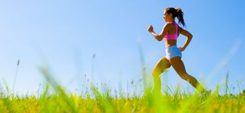 Athletic Woman Exercising. Athletic woman working out in a meadow, from a complete series of photos Royalty Free Stock Photo