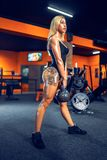 Athletic woman exercising with kettle bell while being in squat position. royalty free stock photo
