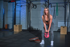 Athletic woman exercising with kettle bell while being in squat position. Bonde woman doing crossfit workout at gym. Stock Image
