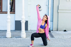 Athletic woman exercising turkish get up with kettlebell Royalty Free Stock Image