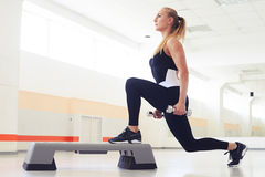 Athletic woman exercising with weights on step aerobics. Young woman holding dumbbells while being in squat position in a health club. Fitness, sport, training Royalty Free Stock Photography