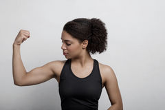 Athletic woman flexing her arm muscle. In studio stock photo