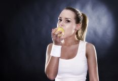 Athletic woman hands ripe yellow apple Royalty Free Stock Photography