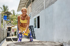 Athletic woman hit a tire by the hammer. Crossfit.  Royalty Free Stock Images