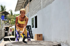 Athletic woman hit a tire by the hammer. Training on the street, Royalty Free Stock Photography