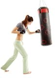 Athletic woman hitting the punching bag Stock Photos