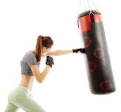 Athletic woman hitting the punching bag Royalty Free Stock Photos