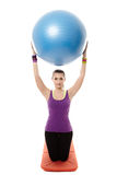 Athletic woman holding a ball and doing stretching Stock Photos
