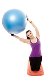 Athletic woman holding a ball and doing stretching Stock Images