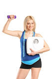 Athletic woman holding a dumbbell and weight scale Royalty Free Stock Photo