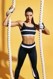 Athletic woman holding heavy ropes and looking at camera. Stock Images