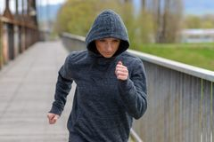 Athletic woman in a hoodie jogging across a bridge Stock Photography