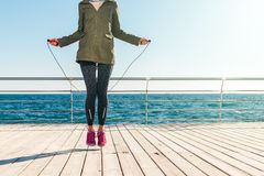 Athletic woman in a jacket and sneakers jumps rope in the mornin. G on the background of the sea, low angle shooting Royalty Free Stock Photo