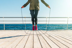 Athletic woman in a jacket and sneakers skipping rope in the mor. Ning on the beach, low angle shooting Stock Photos