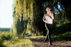 Athletic woman jogging in nature stock photos