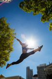 Athletic woman jumping in the air and doing split Royalty Free Stock Images