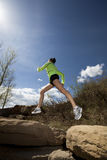 Athletic Woman Jumping While Jogging. Athletic young woman jumping across boulders while out jogging stock images