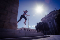 Athletic woman jumping off the stairs Royalty Free Stock Photos
