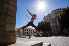 Athletic woman jumping off the stairs Stock Image