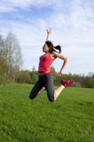 Athletic woman jumping in the park Stock Photos