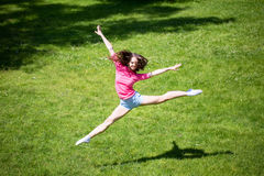 Athletic woman jumping in the park. Stock Photo