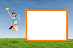 Athletic woman jumps next to empty board Stock Photos