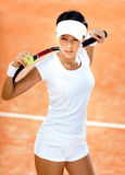 Athletic woman keeps tennis racket. Woman in sports wear keeps tennis racket and ball on her shoulders at the clay tennis court. Tournament Stock Image