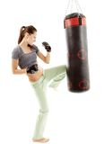 Athletic woman kicking the punching bag royalty free stock photo