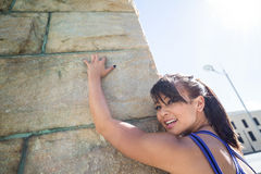 Athletic woman leaning against wall Stock Images