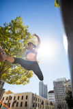 Athletic woman leaping and holding arms up in the air Stock Photography