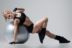 Athletic woman lies on a gym ball royalty free stock images
