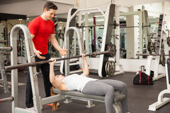 Athletic woman lifting a barbell in a gym. Young athletic women lifting a barbell on a bench press while her personal trainer spots her at a gym Stock Photography