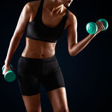 Athletic woman lifting dumbbell Royalty Free Stock Image