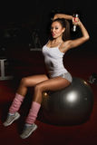 Athletic woman Lifting Weights. Woman Lifting Weights on Pilates ball workout posture in fitness club royalty free stock photography