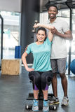 Athletic woman lifting weights helped by trainer Royalty Free Stock Photo