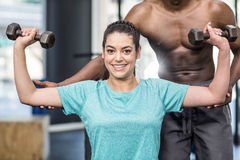 Athletic woman lifting weights helped by trainer Stock Photo