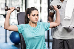 Athletic woman lifting weights helped by trainer Stock Photography