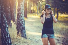 Athletic woman listening music on a running in forest Stock Photography
