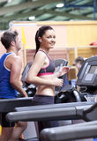 Athletic woman listening to the music on treadmill Royalty Free Stock Images